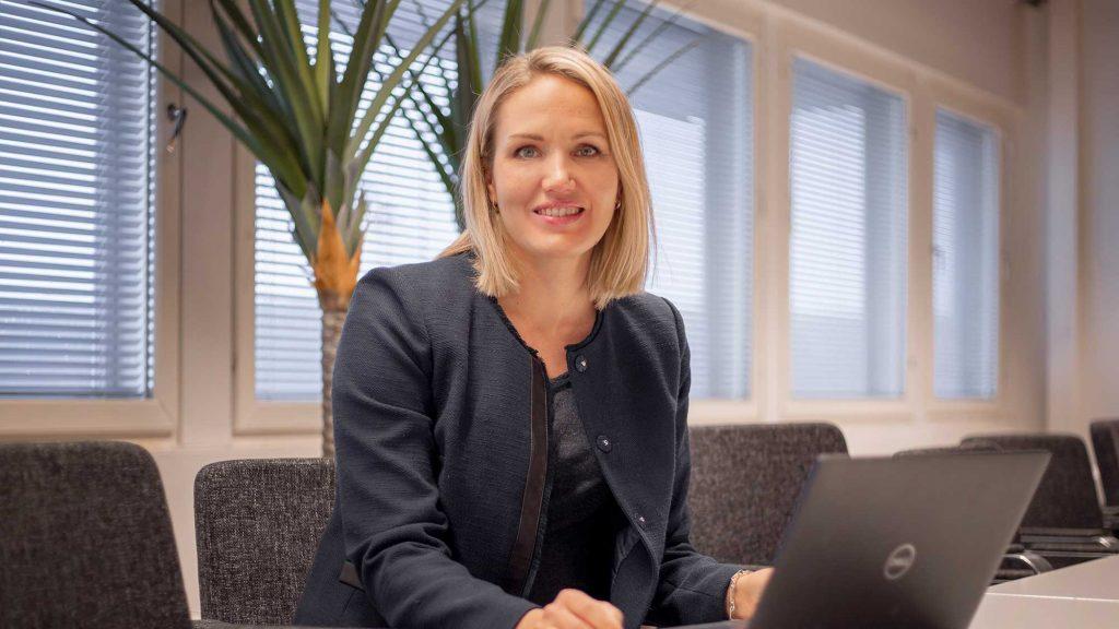 Vaaleahiuksinen nainen istuu neuvotteluhuoneessa kameraan katsoen